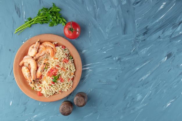 Crevettes et vermicelles dans un bol, sur fond de marbre.