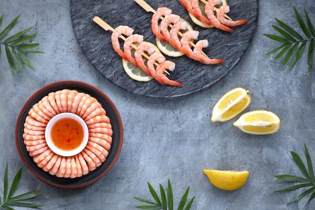 Crevettes zestées au citron et à l'ail sur des bâtons en bois et une assiette sombre avec une sauce chili douce, à plat sur du noir