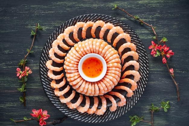 Crevettes zestées au citron et à l'ail servies sur une assiette sombre avec une sauce chili douce, à plat sur du noir