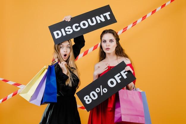Criant de jeunes femmes avec signe de réduction 80% et sacs colorés isolés sur jaune avec du ruban adhésif