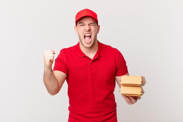 Crier agressivement avec une expression de colère ou avec les poings serrés célébrant le succès