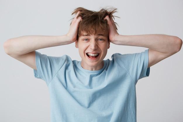 Crier étonné et excité jeune homme agrippé à sa tête