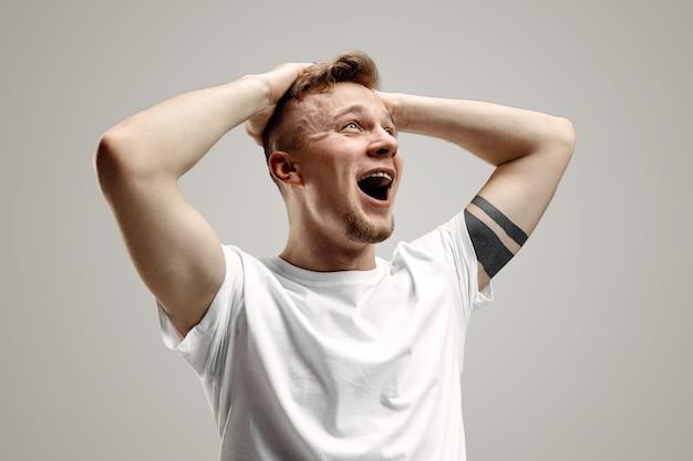 Crier, haine, rage. pleurer un homme en colère émotionnel criant sur fond gris de studio. visage jeune et émotionnel. portrait de demi-longueur masculine. émotions humaines, concept d'expression faciale.