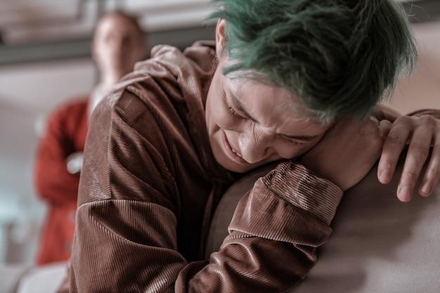 Crier à haute voix. jeune femme aux cheveux verts criant à haute voix après une dispute avec un mari en colère