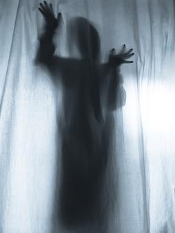 Crier l'homme en appuyant sur un rideau de tissu comme arrière-plan d'horreur