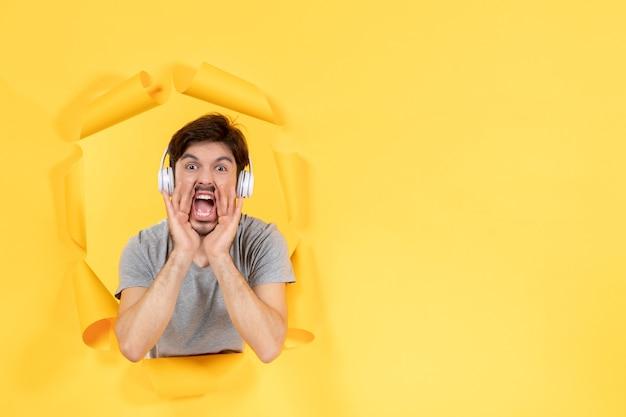 Crier jeune homme dans les écouteurs sur fond de papier jaune son ultrasonore audio