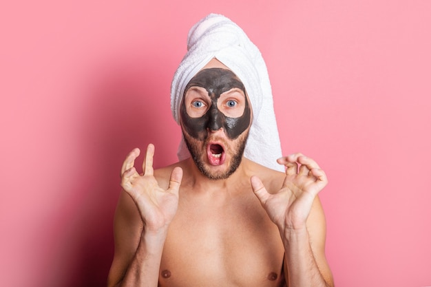 Crier jeune homme avec masque cosmétique sur son visage sur fond rose