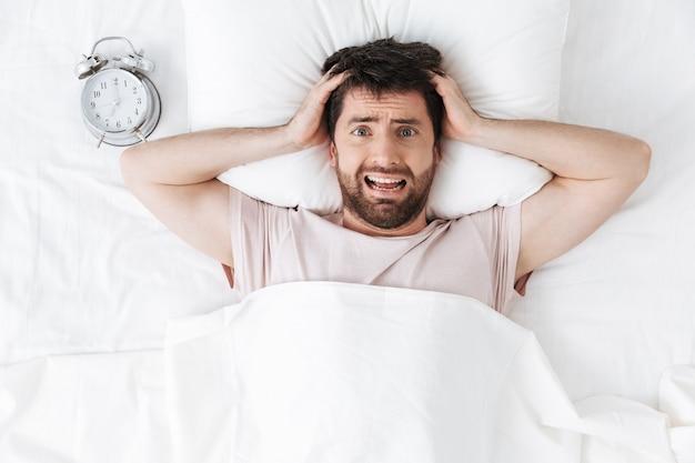 Crier mécontent jeune homme le matin sous une couverture dans le lit se trouve