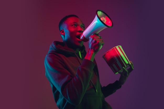 Crier le portrait de l'homme afro-américain sur fond de studio dégradé à la lumière du néon