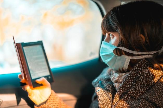 Crise de santé covid-19, caucasien voyageant lisant un livre électronique avec un masque à l'intérieur d'une voiture