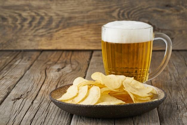 Crisp dans un bol avec de la bière dans un verre, vue de dessus, en bois, espace de copie
