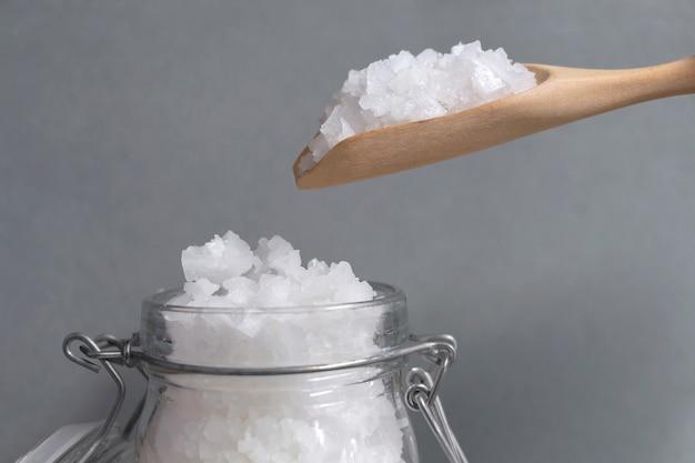 Cristaux blancs de sel de mer dans des bouteilles en verre et sur une cuillère en bois