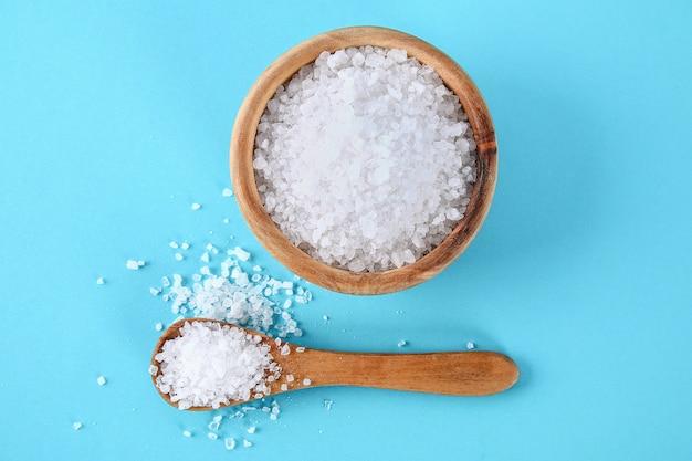 Cristaux de gros sel de mer dans un bol en bois et une cuillère sur une table bleue.