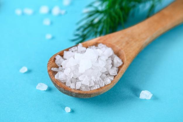Cristaux de gros sel de mer dans une cuillère en bois et aneth sur une table bleue.