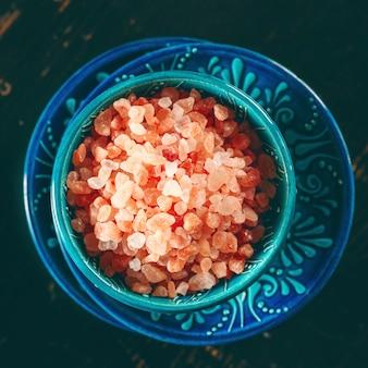 Cristaux de sel rose de l'himalaya dans un bol authentique
