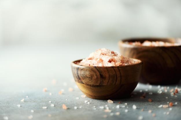 Cristaux de sel rose de l'himalaya et poudre dans des bols en bois sur béton gris. alimentation saine sans sel.