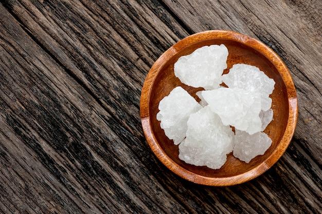 Cristaux de sucre cristallin sur un vieux bois. vue de dessus, pose à plat.