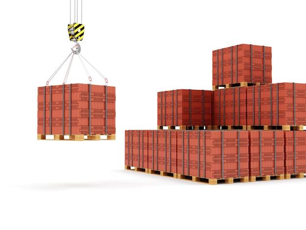 Crochet de grue avec des briques rouges empilées sur une palette en bois isolé