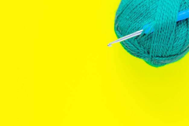 Un crochet en métal avec une poignée bleue est inséré dans un écheveau de fil vert dans le coin supérieur du p...