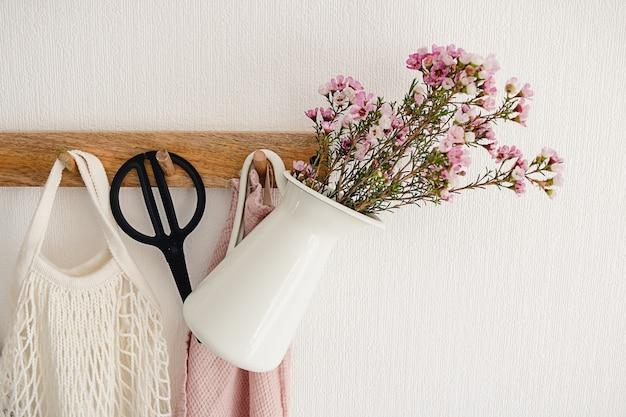 Crochet de suspension avec pot de bouquet de fleurs violettes, ciseaux noirs, balai et pelle accroché sur un mur blanc dans la cuisine moderne. concept de vie minimaliste écologique
