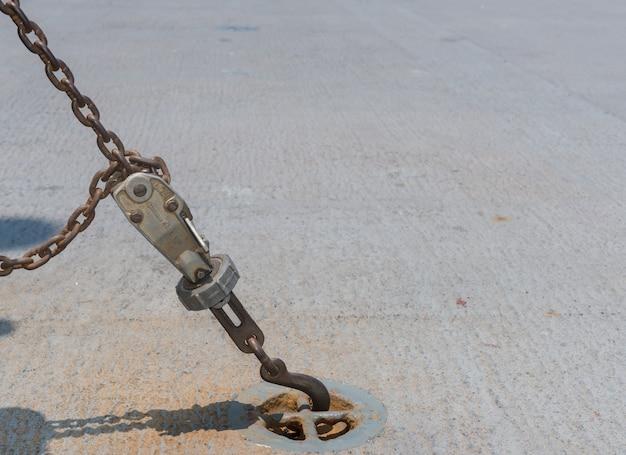 Crochet vieux rouillé et chaîne sur un fond de sol.