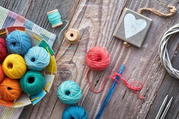 Crochet, vue de dessus sur des boules de laine sur bois rustique