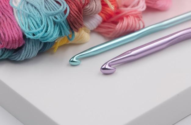Crochets cochet mis à côté de fils colorés, lumière floue aorund
