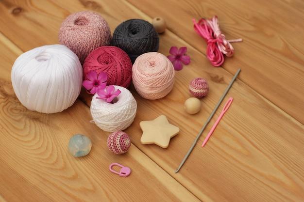 Crochets et fils gris blanc rose au crochet, espace de copie de fond en bois.