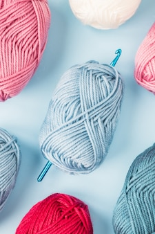Crochets multicolores avec des pelotes de laine sur fond bleu