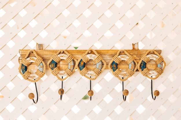 Crochets à vêtements dans le couloir, en forme de sauveteurs, enveloppés de corde et avec des pointes en bois