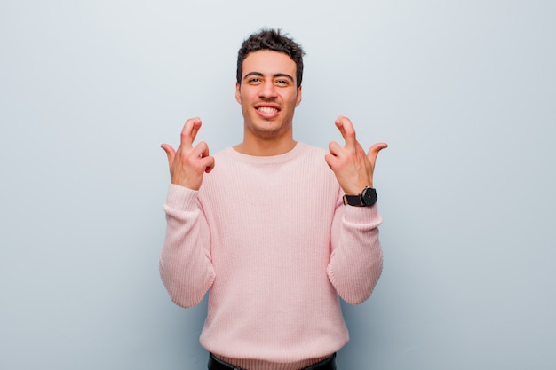 Croisant les doigts avec anxiété et espérant bonne chance avec un regard inquiet