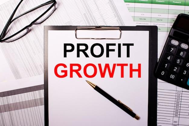 La croissance des bénéfices est écrite sur une feuille de papier blanc, près des verres et de la calculatrice