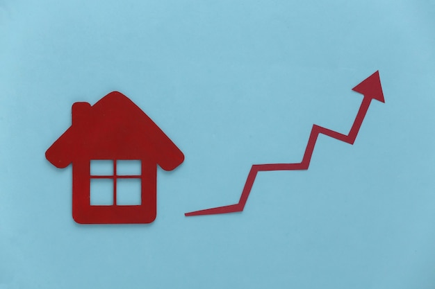 Croissance des prix des logements. figurine de maison et flèche de croissance tendant vers le haut sur un bleu