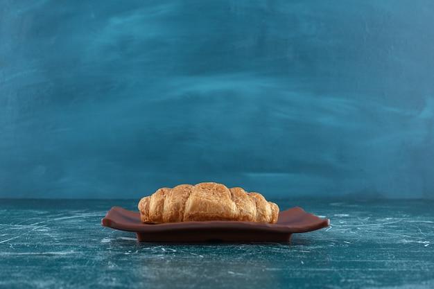 Croissant sur une assiette brune, sur la table bleue.