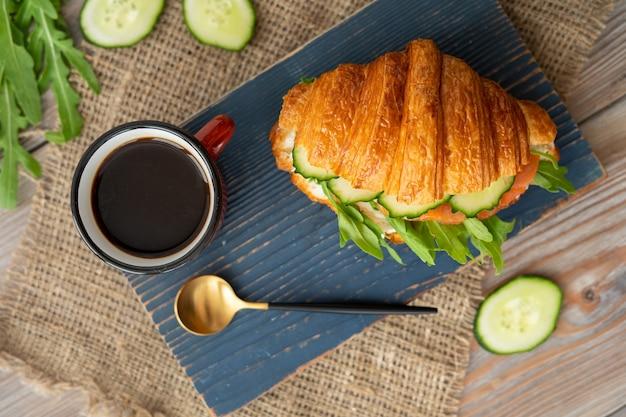 Croissant au concombre, laitue et sandwich au saumon avec une tasse de café sur un bureau en bois bleu