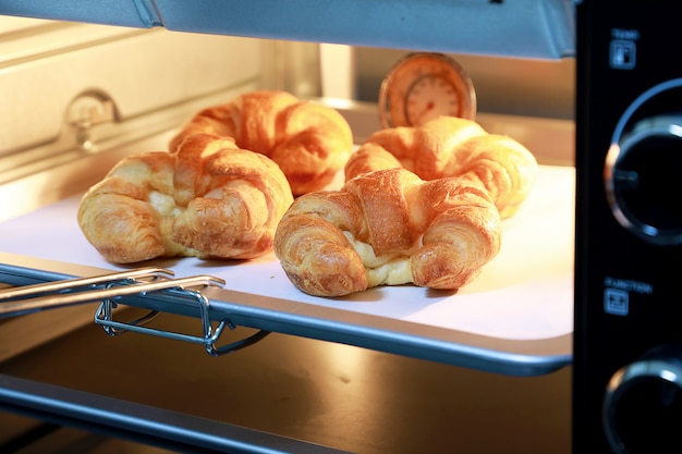 Croissant au fromage au four avec des lumières chaudes du four.