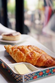 Croissant au fromage bleu servi avec du beurre. assiette de petit déjeuner avec des croissants fraîchement cuits
