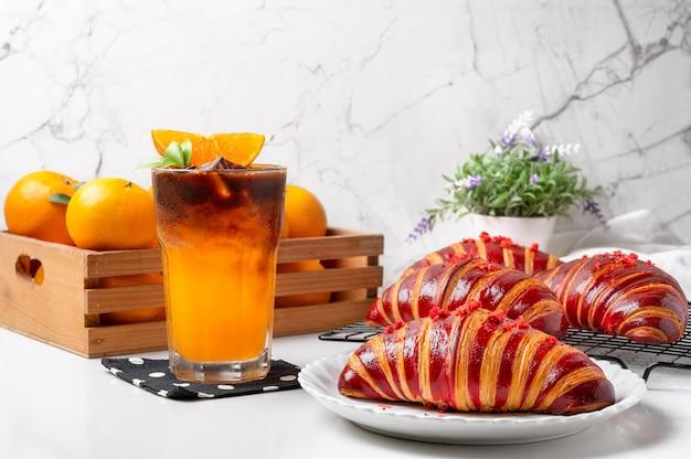 Le croissant aux framboises avec du café américain à l'orange est prêt à servir le matin, rafraîchissant.