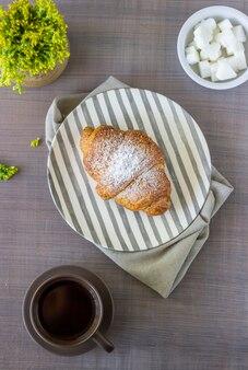 Un croissant et un café sur un gris. les fleurs. petit déjeuner.