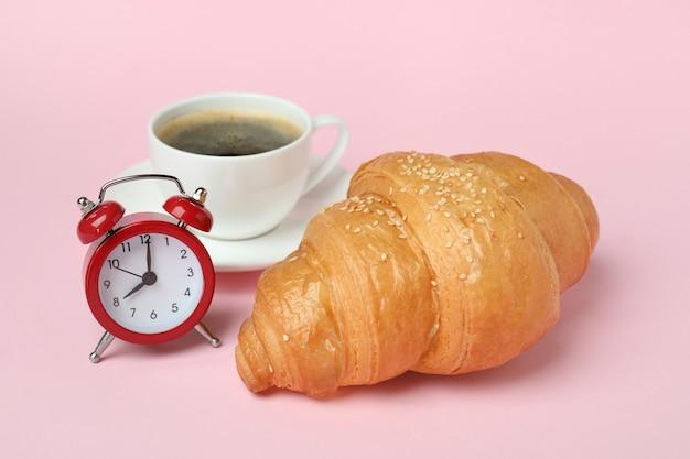 Croissant, café et réveil sur rose