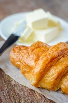 Croissant close-up et beurre sur une table en bois