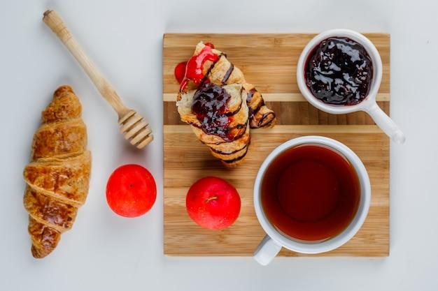 Croissant avec confiture, prunes, louche, thé blanc et planche à découper, pose à plat.