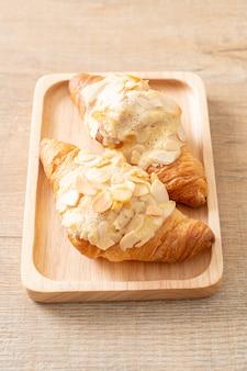 Croissant à la crème et aux amandes sur plaque de bois