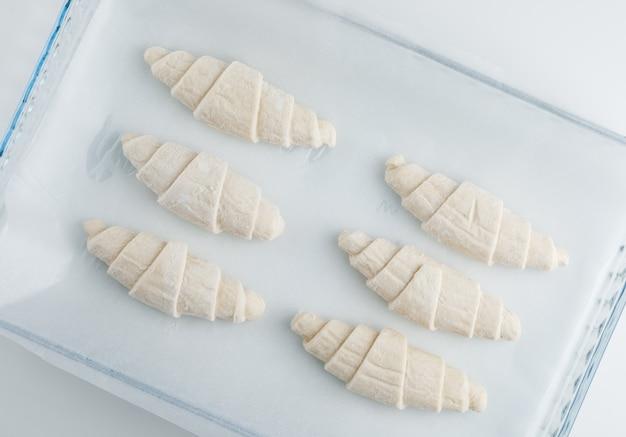 Croissant cru dans un sac en plastique sur table blanche, pose à plat.