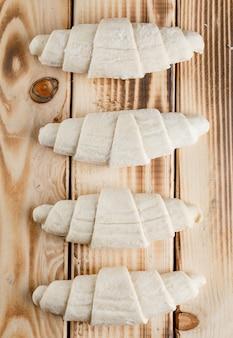 Croissant cru sur table en bois, pose à plat.