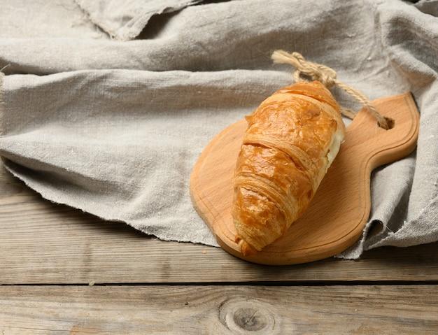 Croissant cuit au four sur planche de bois, table grise en bois, gros plan, vue du dessus