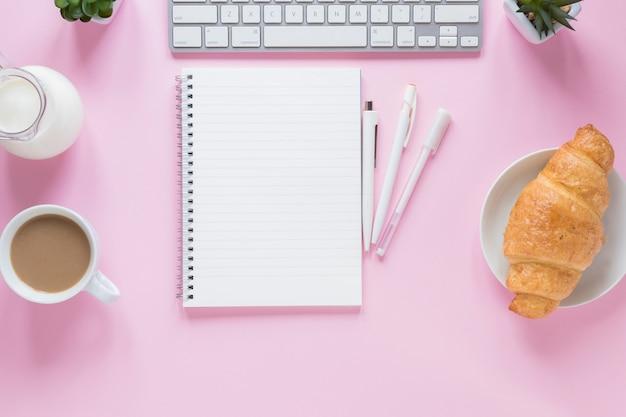 Croissant cuit au four; tasse de thé; lait avec clavier et fournitures de bureau sur fond rose