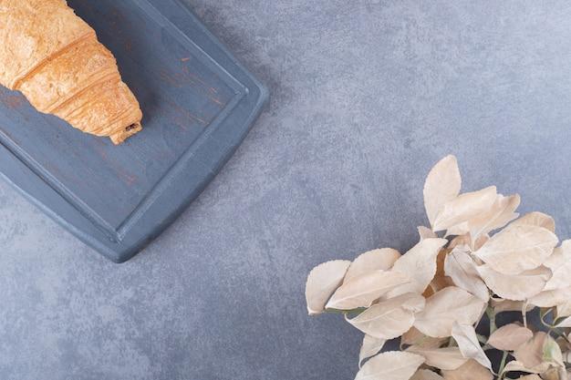 Croissant délicieux fraîchement sorti du four sur planche de bois. fermer.