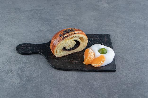Croissant demi-coupé avec des tranches de mandarine sur une planche à découper noire.