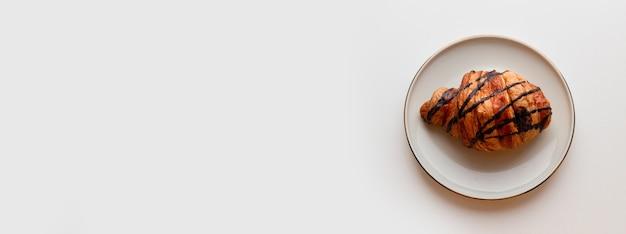 Croissant fraîchement sorti du four avec garniture au chocolat sur plaque sur fond gris. mise à plat, vue de dessus, espace copie